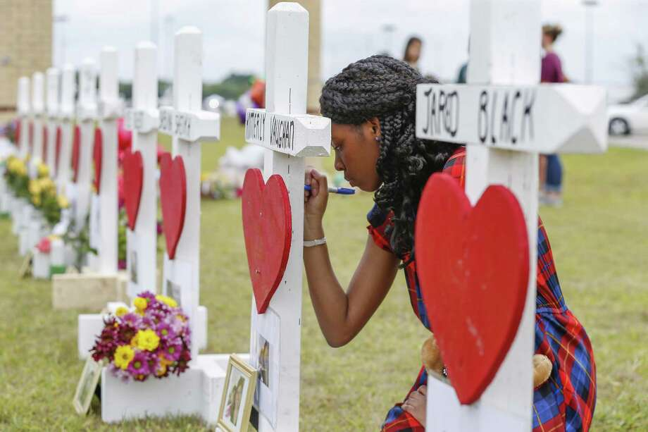 Santa Fe High School freshman Jai Gillard writes messages on each of the 10 crosses for those killed in the mass shooting at the school. The Texas Education Agency is asking lawmakers for $54 million to fund school safety initiatives in the next two years. Photo: Steve Gonzales, Houston Chronicle / Houston Chronicle / © 2018 Houston Chronicle