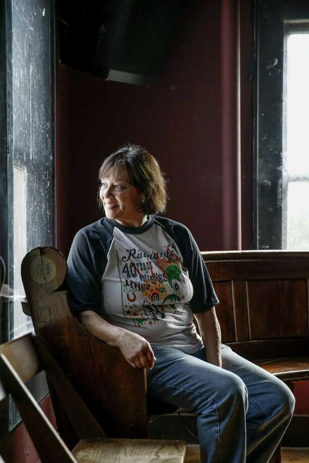 Rudyard's British Pub owner Lelia Rodgers sits on a bench from a London train station in the bar Friday Aug. 24, 2018 in Houston. The pub is celebrating its 40th year anniversary this year. Photo: Michael Ciaglo, Houston Chronicle / Staff Photographer / Michael Ciaglo