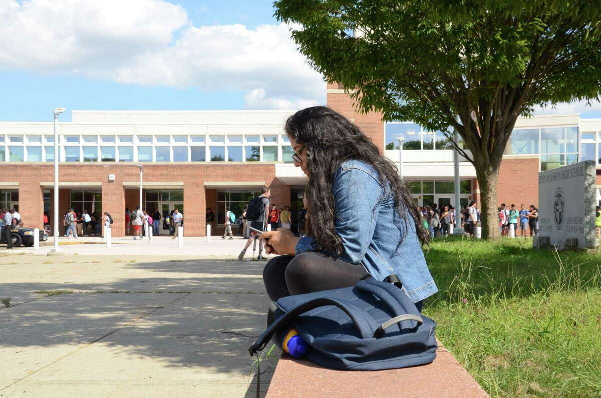 Student, Maria Gomez uses her cell phone after school Thursday at Brien McMahon High School. The 12th-grader says the school's new cell phone policy, which bans usage during class, will affect younger students, who are more preoccupied with the latest iPhone apps.