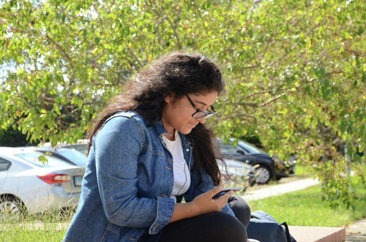 Student, Maria Gomez uses her cell phone after school Thursday at Brien McMahon High School. The 12th grader says the school's new cell phone policy, which bans usage during class, will affect younger students, who are more preoccupied with the latest iphone updates.