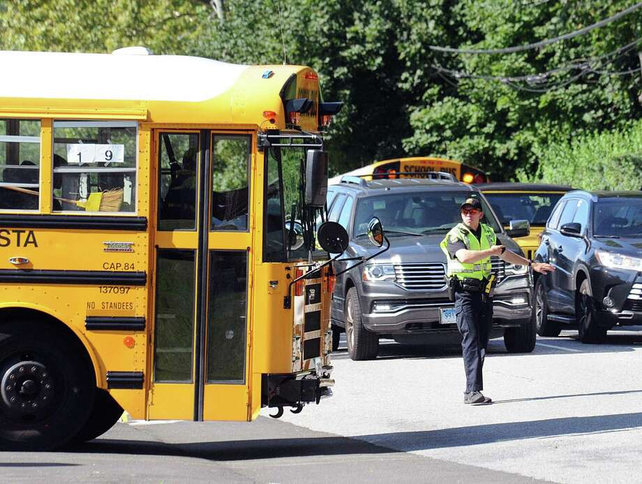 A Greenwich police officer directs traffic on Hillside Road in front of Greenwich High School during dismissal on the first day of school in Greenwich, Conn., Thursday, Agust 30, 2018. Photo: Bob Luckey Jr. / Hearst Connecticut Media / Greenwich Time