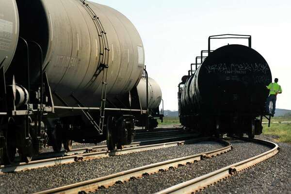 f44e956d8b0 3of3Hondo Railway worker rides on a tanker car as rail cars are moved to be  unloaded. The company has seen growth with the increased business from the  Eagle ...