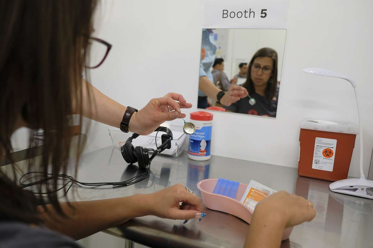 In this photo taken Wednesday, Aug. 29, 2018, volunteer Rachele Huennekens sits at a booth injection station during a demonstration at Safer Inside, a realistic model of a safe injection site in San Francisco. The model is an example of a supervised, indoor location where intravenous drug users can consume drugs in safer conditions and access treatment and recovery services. (AP Photo/Eric Risberg)