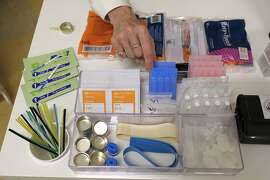 In this photo taken Wednesday, Aug. 29, 2018, Linda Montel shows off supplies on a check in desk at Safer Inside, a realistic model of a safe injection site in San Francisco. The model is an example of a supervised, indoor location where intravenous drug users can consume drugs in safer conditions and access treatment and recovery services. (AP Photo/Eric Risberg)