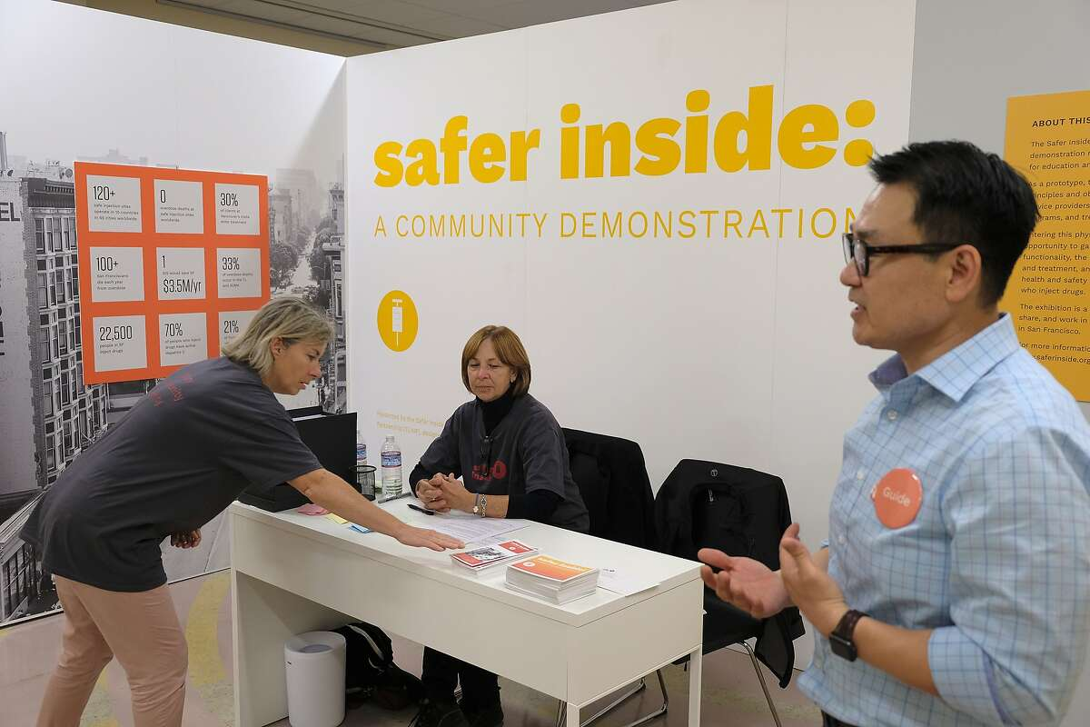In this photo taken Wednesday, Aug. 29, 2018, Marie Fauvel, left, and Pat Shea, center, talk at a reception desk at Safer Inside, a realistic model of a safe injection site in San Francisco. At right giving a tour is clinical director Kenneth Kim. The model is an example of a supervised, indoor location where intravenous drug users can consume drugs in safer conditions and access treatment and recovery services. (AP Photo/Eric Risberg)