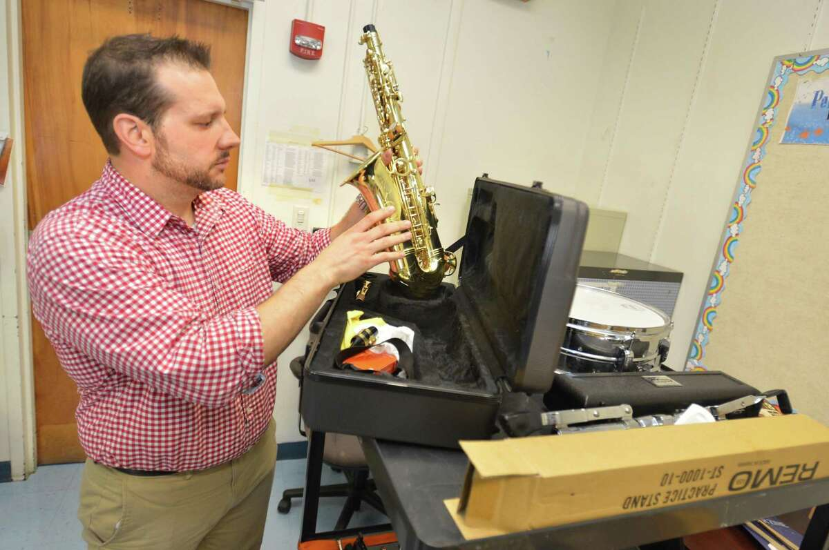 Anthony Nunes, fourth- and fifth-grade band teacher at Columbus Magnet and Rowayton schools, looks over one of the alto saxaphones for his students at Columbus School on Tuesday.