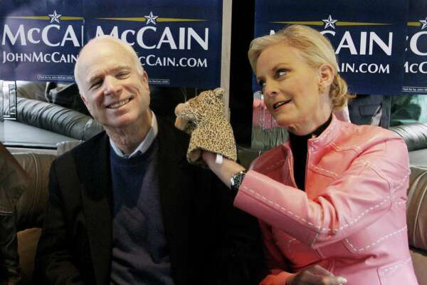"""Cindy McCain, wife of Republican presidential hopeful Sen. John McCain, R-Ariz., uses a cheetah hand puppet to make her husband laugh as they ride the """"Straight Talk Express"""" campaign bus in 2008 to a polling station in Charleston, S.C. McCain's patriotism will be missed."""