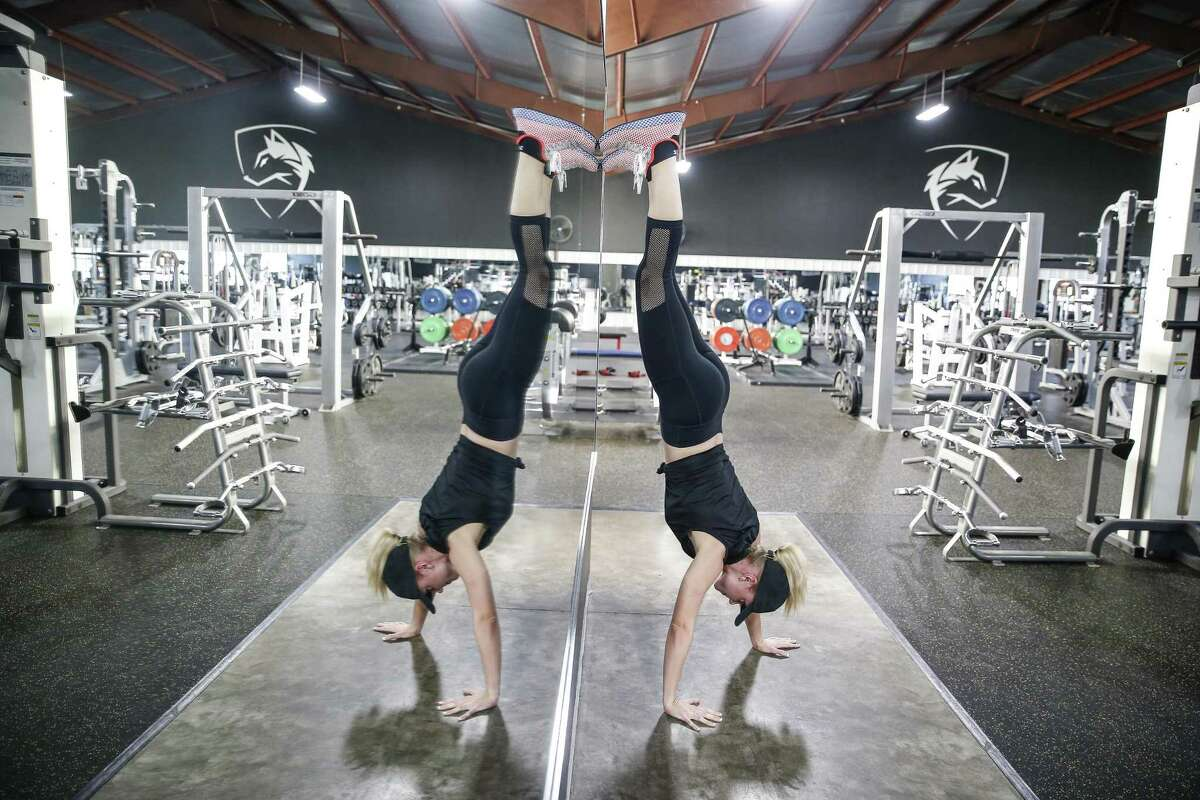 Fox 26 reporter Ivory Hecker does a handstand walk as she works out at Alphalete Gym Thursday Aug. 30, 2018 in Stafford.