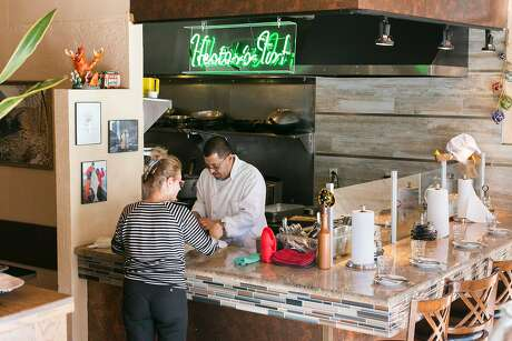 At Betty Lou's Seafood and Grill in North Beach, chef Hector Chaparro and Louise Taylor garnish a dish. Photo: Jen Fedrizzi, Special To The Chronicle