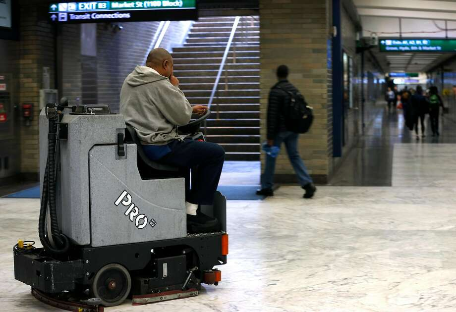 FILE: A maintenance worker cleans the floor at the Civic Center BART station in San Francisco, Calif. on Tuesday, June 19, 2018. The station closed Wednesday due to flooding. Photo: Paul Chinn / The Chronicle