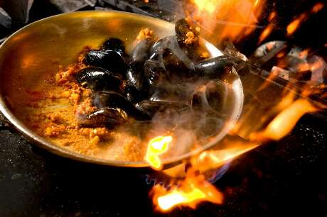 Chorizo and mussels get a quick toss on the stove at Don Pisto's in North Beach. Photo: Chad Ziemendorf / The Chronicle