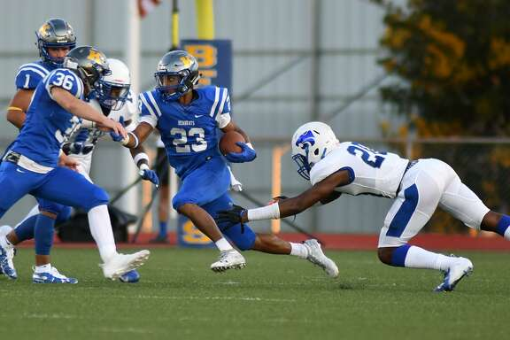 Klein senior running back D'Anthony Simms (23) tries to escape a pair of Cy Creek defenders with help from teammates Cameron Kaiser (36) and Tyson Thompson (1) during the first quarter of their football season opener at Klein Memorial Stadium on August 30, 2018.