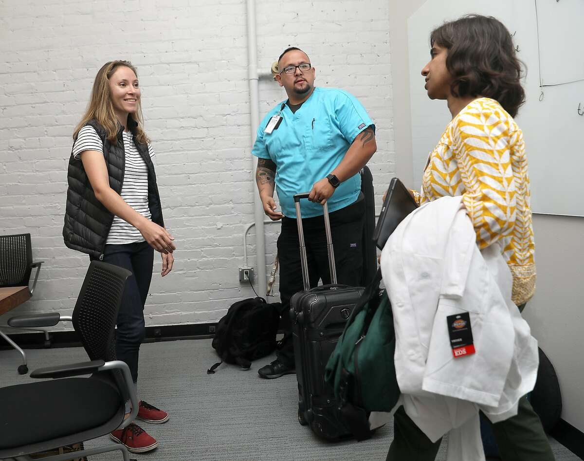 Strava product specialist Camila Ring (left) meets doctor Anju Goel (right) and certified medical assistant Dusty A. Sanabria (middle) in a conference room for her check up at work on Thursday, Aug. 30, 2018 in San Francisco, Calif. Heal, the three-year-old startup that provides doctors who make house calls, is growing by targeting large employers with the goal of sending doctors to see workers at the office.