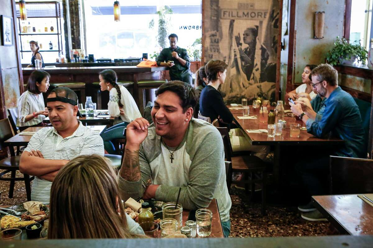 Patrons fill the dining room during lunch at Farmer Brown, one of the last remaining black owned restaurants, as server Astrid Benson walks by in San Francisco, on Friday, August 31, 2018 in San Francisco, Calif.