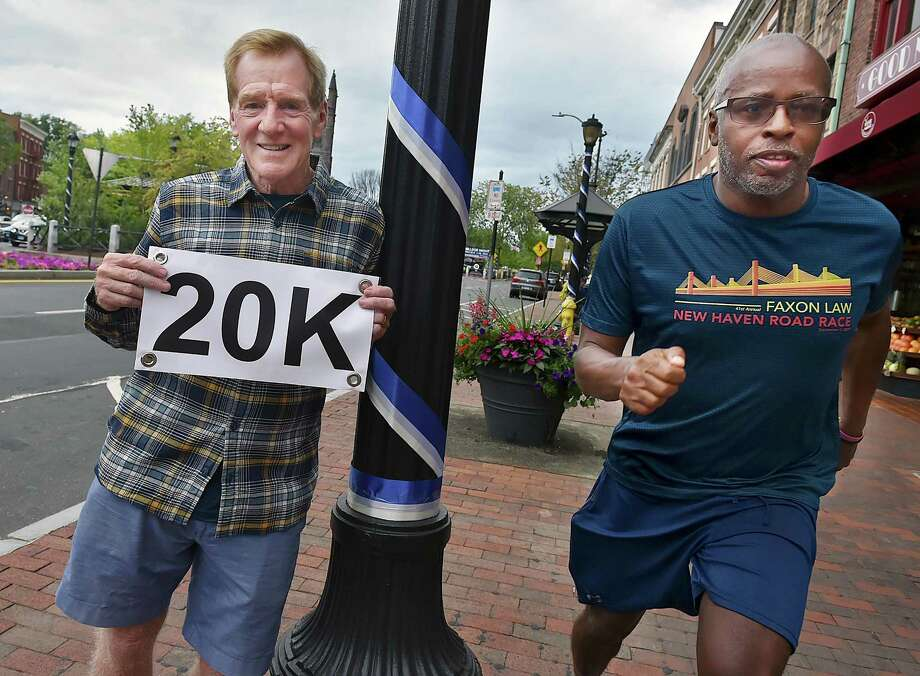 New Haven's John Courtmanche, president of the Board of Directors of the New Haven Road Race is pictured at the city's Broadway shopping district. Running at right is Robert Davis, former track coach at Hillhouse and organizer of the teams of high school and college student volunteers. Photo: Catherine Avalone / Hearst Connecticut Media / New Haven Register