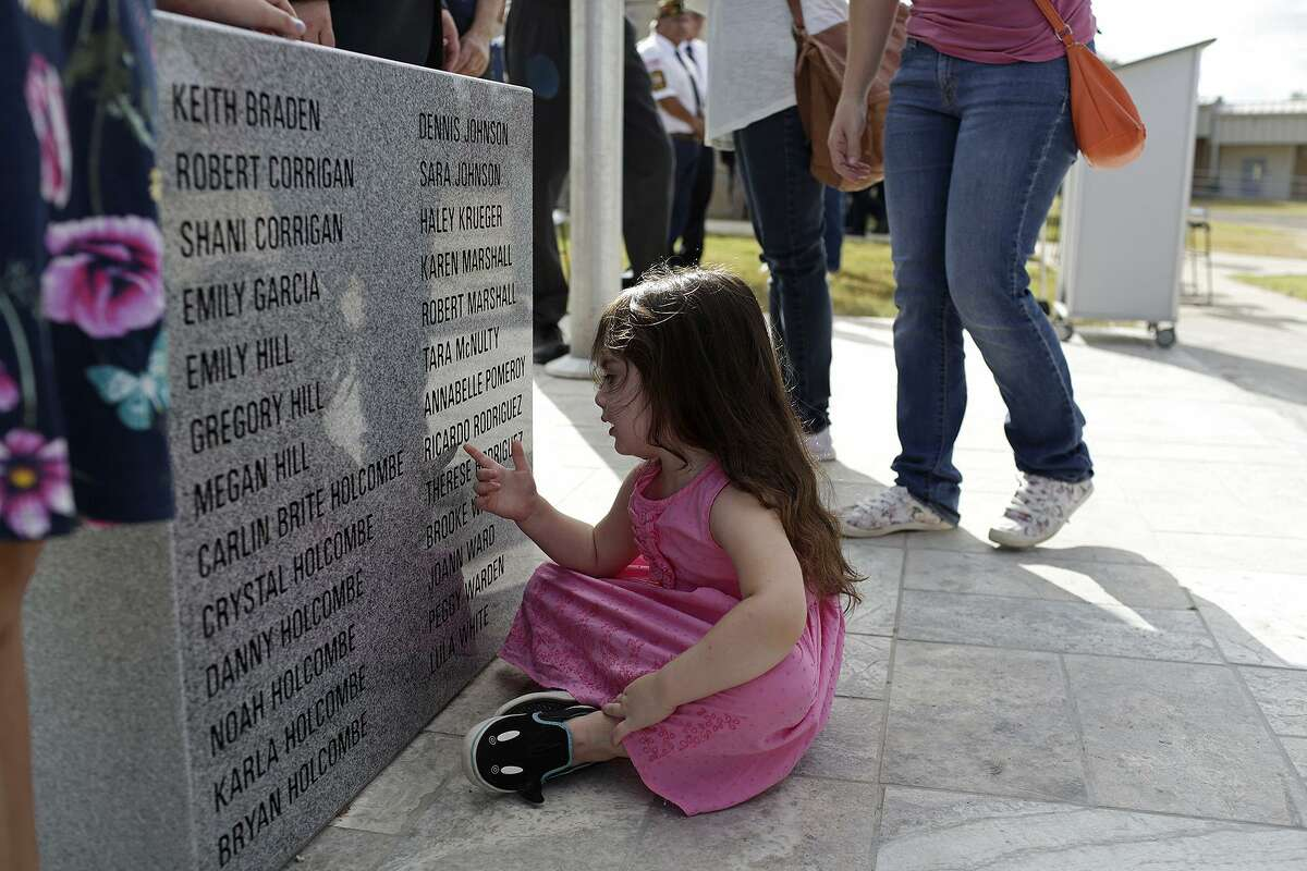 Elene Slavin, 3, a member of the Holcombe family, touches the memorial dedicated to the victims from First Baptist Church of Sutherland Springs, including nine members of her family, Friday at the Wilson County District Court Justice Center in Floresville.