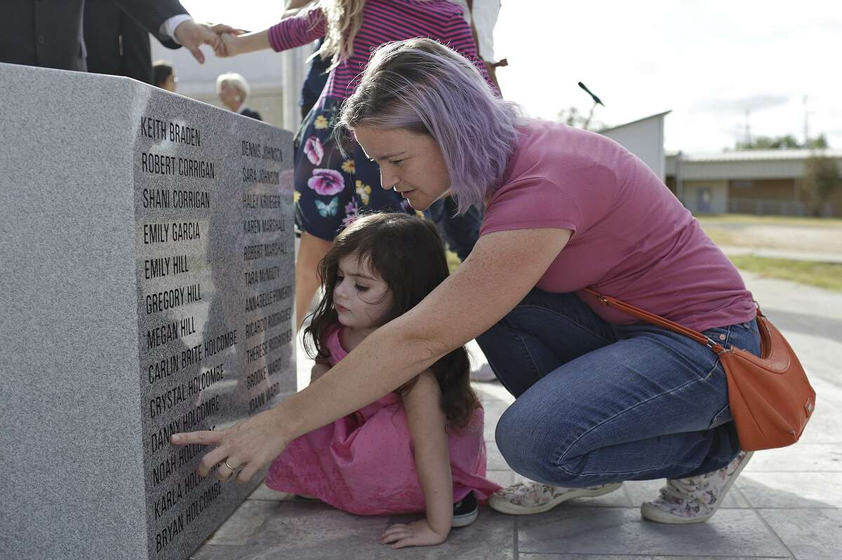 Sarah Slavin points at the name of her brother, Danny Holcombe, as she shows her daughter, Elene Slavin, 3, the nine members of their family listed on the memorial.
