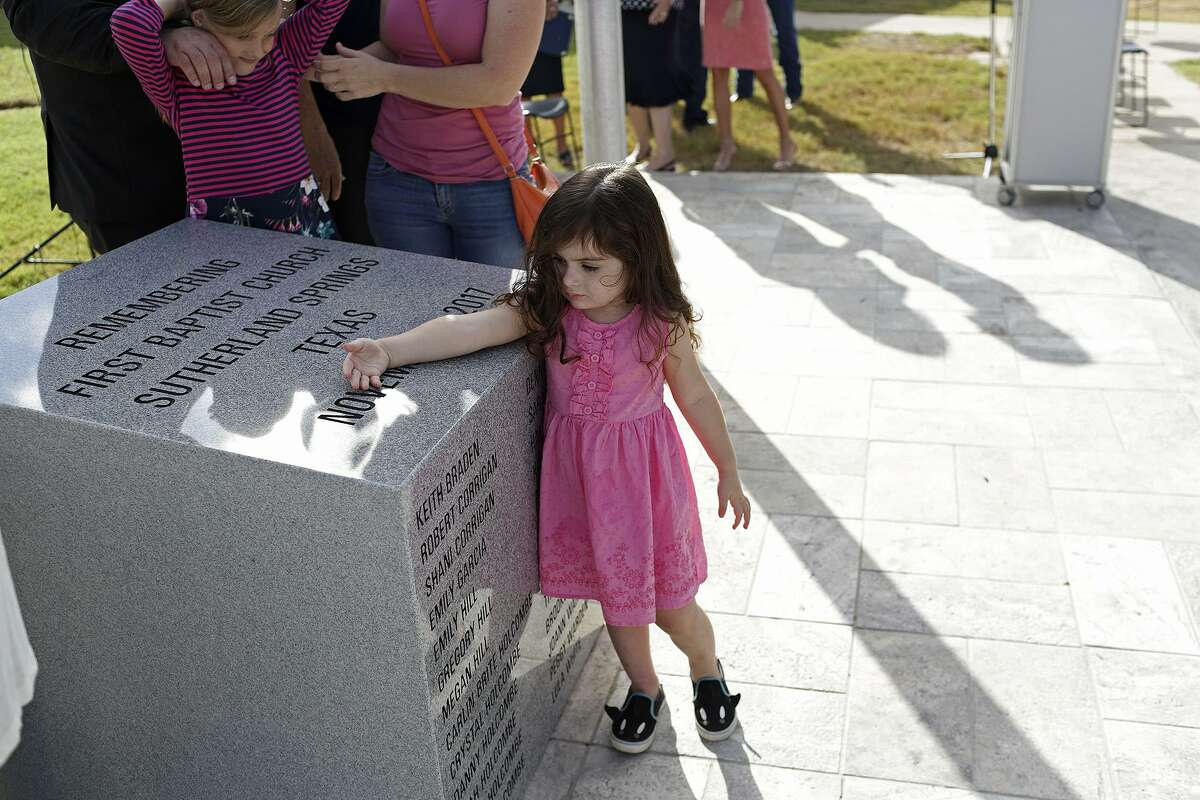 Elene Slavin, 3, a member of the Holcombe family, touches the memorial dedicated to the victims of First Baptist Church of Sutherland Springs. At left is Evelyn Hill, 8, also a member of the Holcombe family.