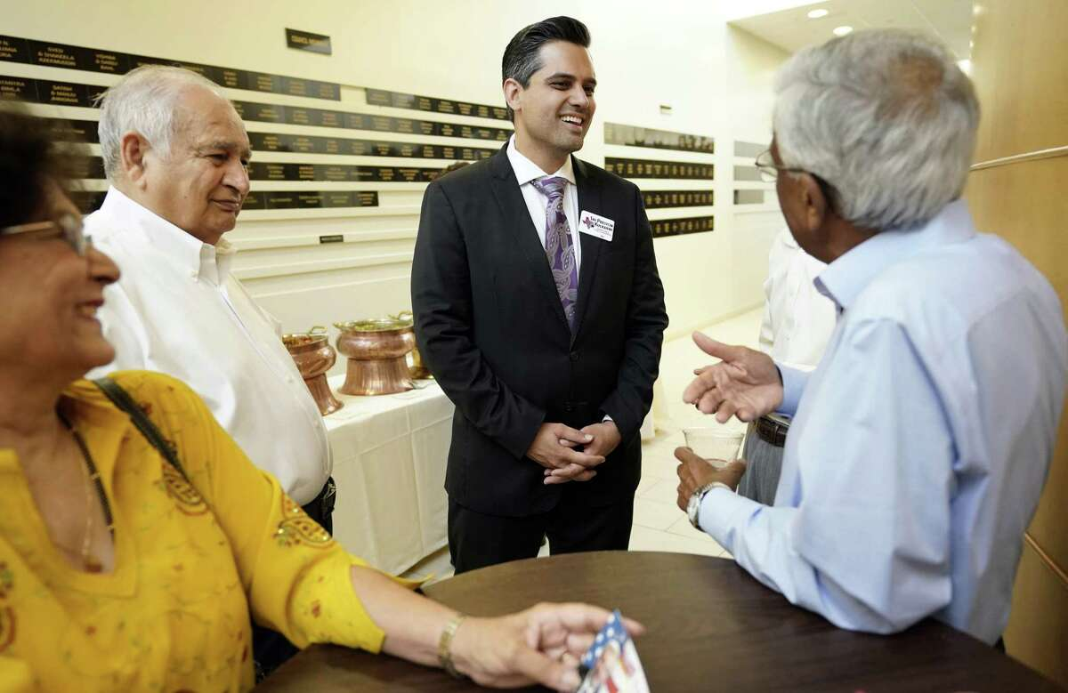 In this Sunday, July 29, 2018, photo, Democrat for Congress candidate Sri Kulkarni, center, listens to supporters attending a fundraiser for him in Houston. Kulkarni is running against Republican U.S. Rep. Pete Olson. (AP Photo/David J. Phillip)