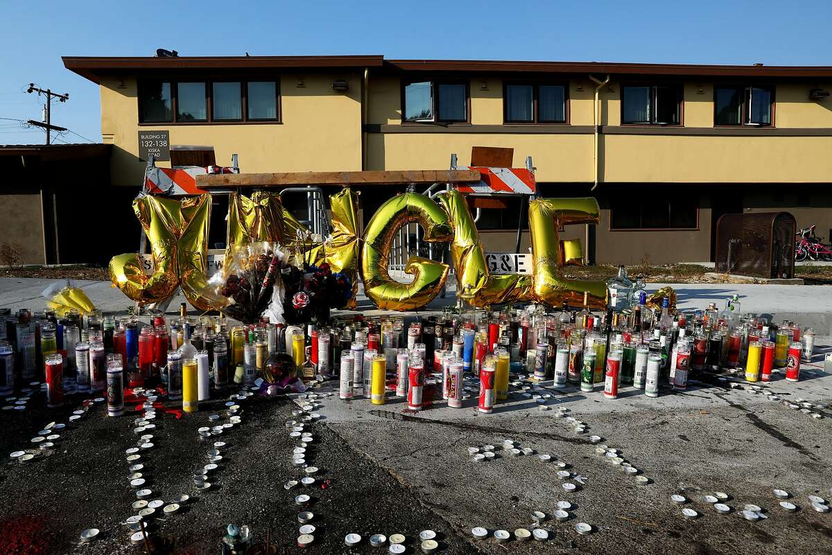 """Gold foil balloons spelling """"JUNGLE"""" rest behind a profusion of candles outside an apartment building in the 100 block of Kiska Rd. in San Francisco, Calif., on Wednesday, August 29, 2018. Earlier this month, Joseph """"Jungle"""" Taeotui, 43, a San Francisco anti-violence community worker, was a victim of a shooting near the Willie Mays Boys and Girls Club in the Bayview District."""