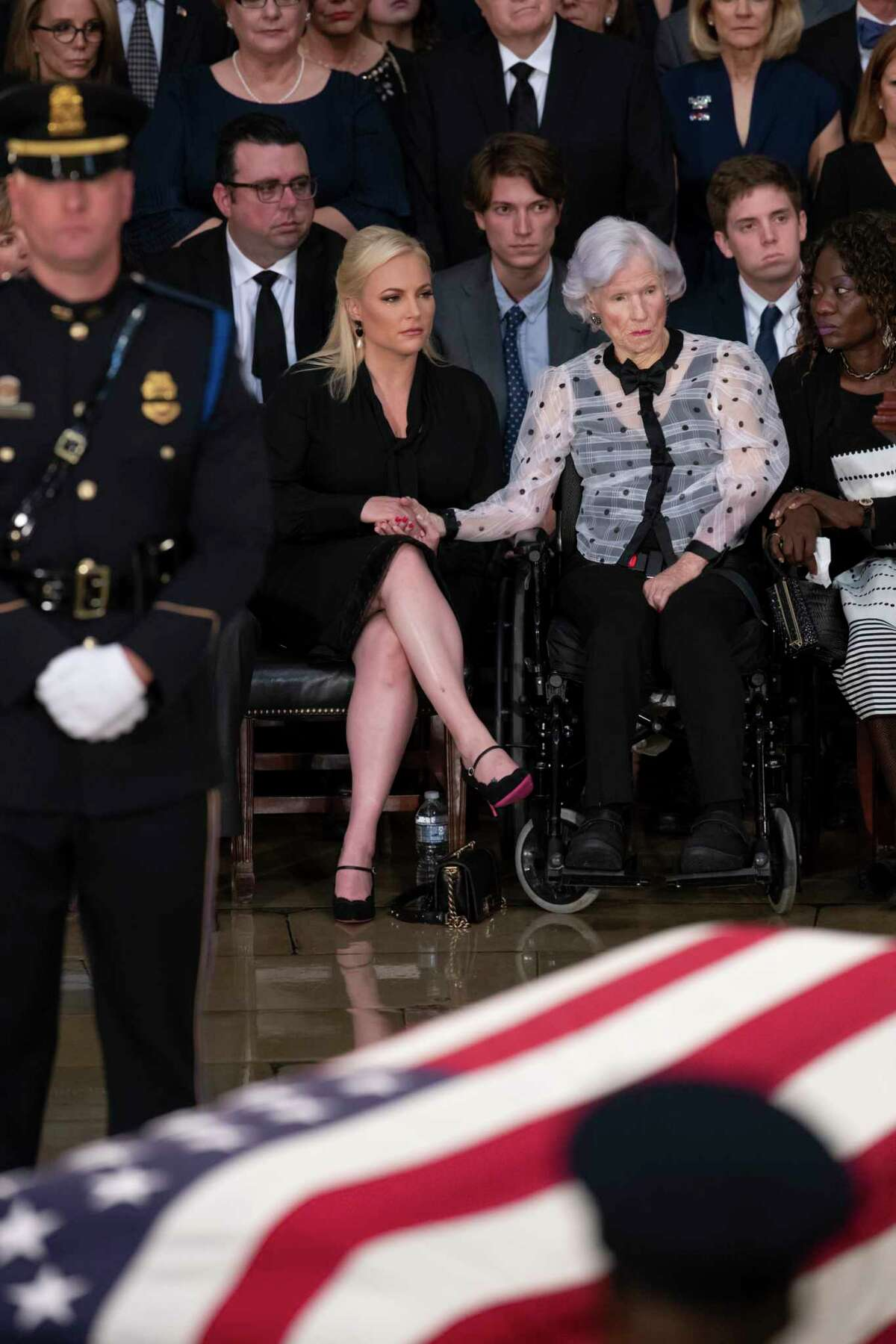 John McCain's daughter Meghan McCain, left, is comforted by his 106-year-old mother Roberta McCain, right, as the flag-draped casket bearing the remains of Sen. John McCain of Arizona, who lived and worked in Congress over four decades, is carried into the U.S. Capitol rotunda for a farewell ceremony and public visitation, Friday, Aug. 31, 2018, in Washington. (AP Photo/J. Scott Applewhite)