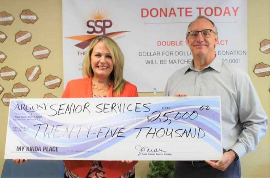 Jonathan Becker, Senior Services Plus CEO, right, and Lynn Marburger, Argosy's community relations manager, pose with the $25,000 check given to SSP from Argosy Casino in support of the construction of its new wellness center. Photo: For The Telegraph