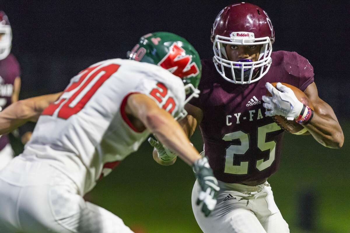 Cy-Fair running back Jaelon Woods (25) runs through the tackle of The Woodlands defensive back Chase Taylor (20) to score his second rushing touchdown of a high school football game at Pridgeon Stadium on Friday, Aug 31, 2018, in Houston.