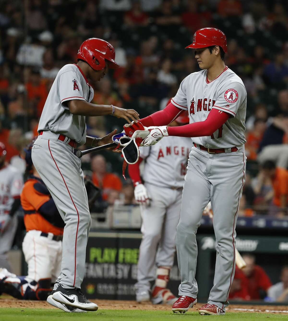 Los Angeles Angels Shohei Ohtani (17) hands his gear to the bat boy as he walked during the ninth inning of an MLB baseball game at Minute Maid Park, Friday, August 31, 2018, in Houston.