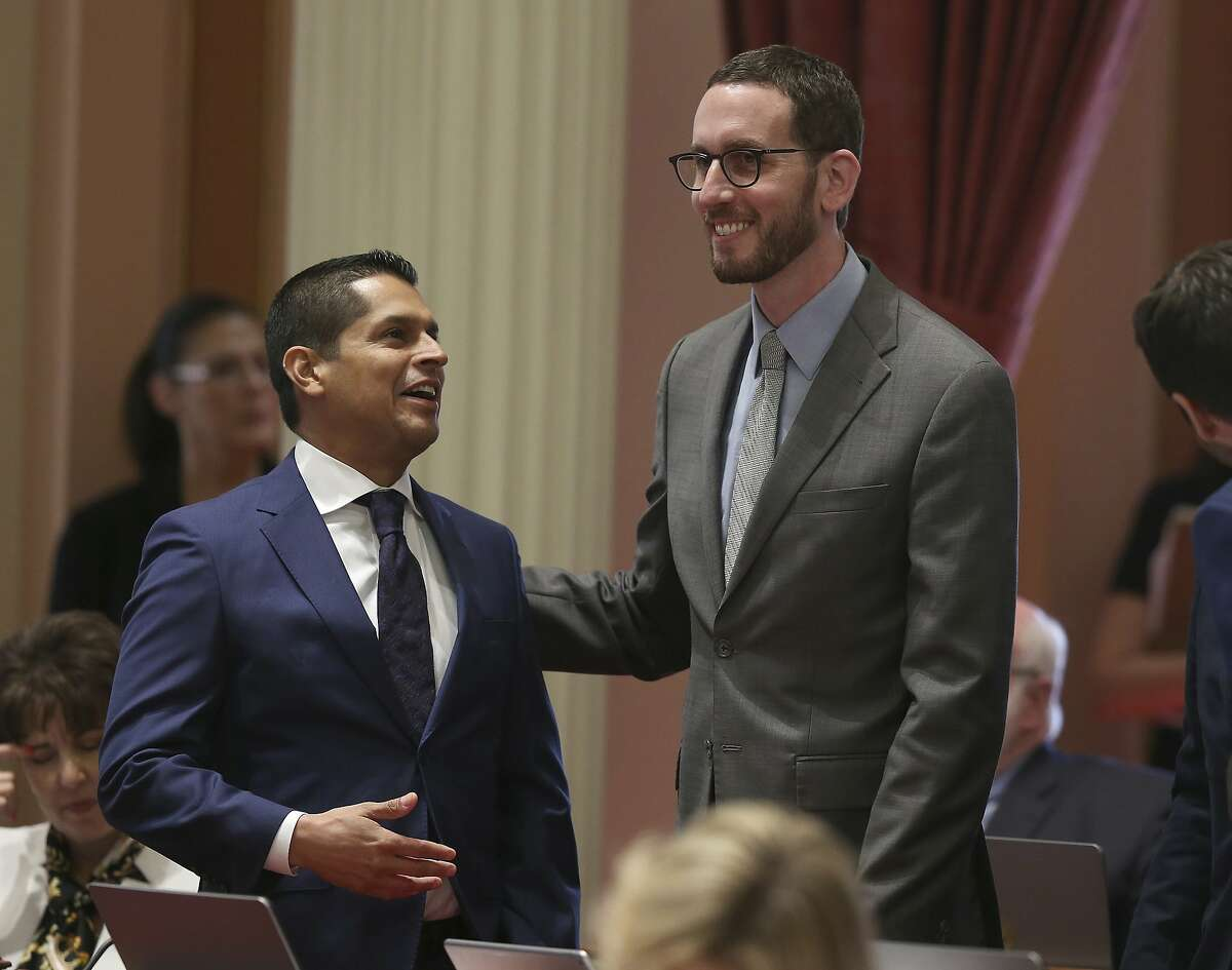 Assemblyman Miguel Santiago, D-Los Angeles, left, and state Sen. Scott Wiener, D-San Francisco, smile after their net neutrality bill was approved by the Senate, Friday, Aug. 31, 2018, in Sacramento, Calif. The bill, which seeks to revive regulations repealed last year by the Federal Communications Commission, now goes to Gov. Jerry Brown. (AP Photo/Rich Pedroncelli)