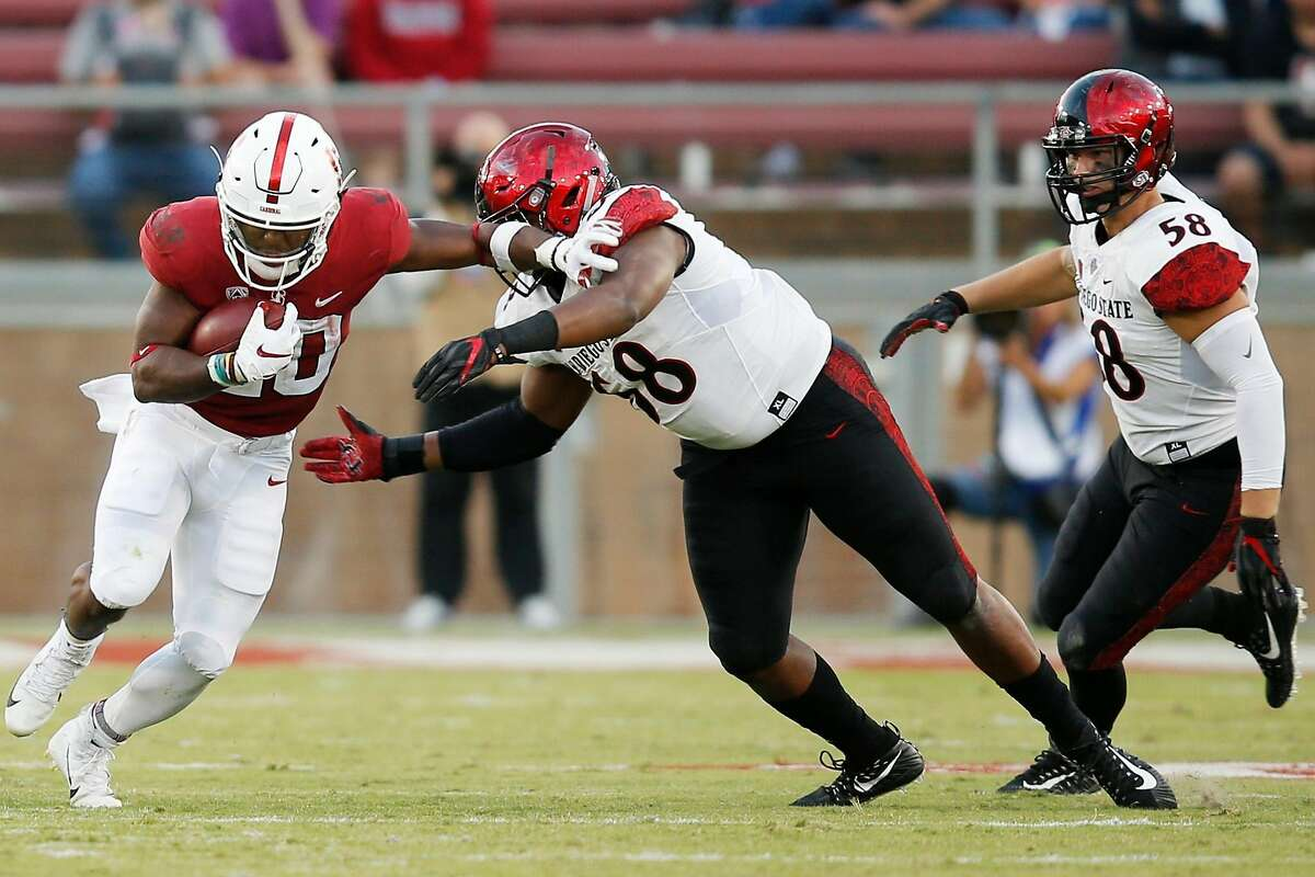 Stanford Cardinal running back Bryce Love (20) stiff arms and evades the tackle for a gain against San Diego State Aztecs defensive lineman Myles Cheatum (68) during an NCAA football game at Stanford Stadium, Friday, Aug. 31, 2018, in Stanford, Calif.