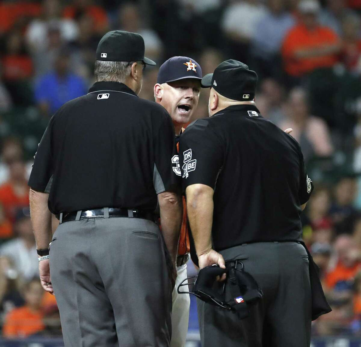 Astros manager A.J. Hinch has a few words for plate umpire Eric Cooper, right, in the fourth inning, also his last Friday.