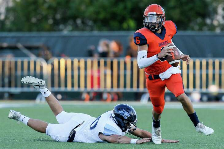 Brandeis quarterback Jordan Battles (right) races past Johnson's Ethan Araujo during the first half of their season-opening high school football game at Farris Stadium on Friday, Aug. 31, 2018. Brandeis beat Johnson 35-17.