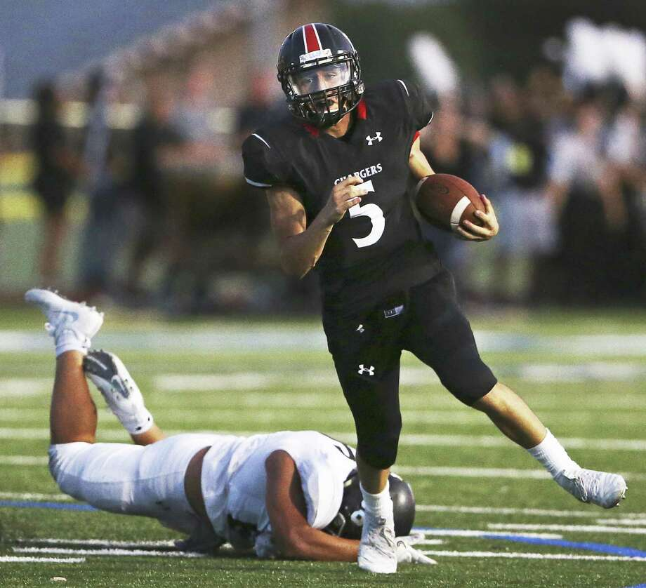 Charger quarterback Derek Perez alludes a tackle on a run around end as Churchill hosts Clark at Comalander Stadium in the Gucci Bowl on August 30, 2018. Photo: Tom Reel, Staff / Staff Photographer / 2017 SAN ANTONIO EXPRESS-NEWS