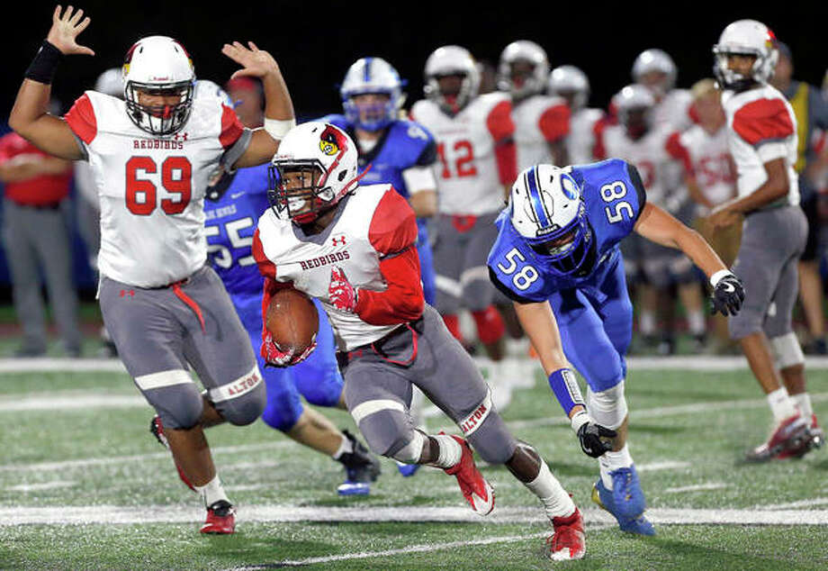 Alton's Ahmad Sanders evades a tackle by Quincy High's Parker Stegeman Friday night at Flinn Stadium in Quincy | Photo: Jake Shane, Quincy Herald-Whig | For The Telegraph