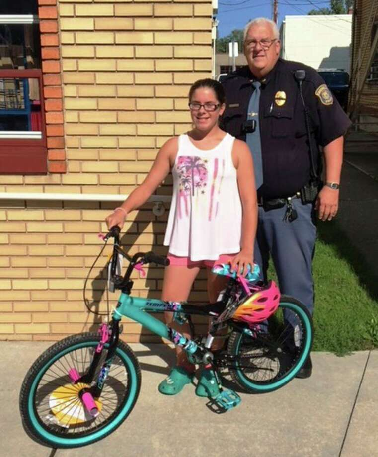 Samantha Tunich receives her bicycle with the help of Croswell Police Chief Dave Hall. (Submitted Photo)