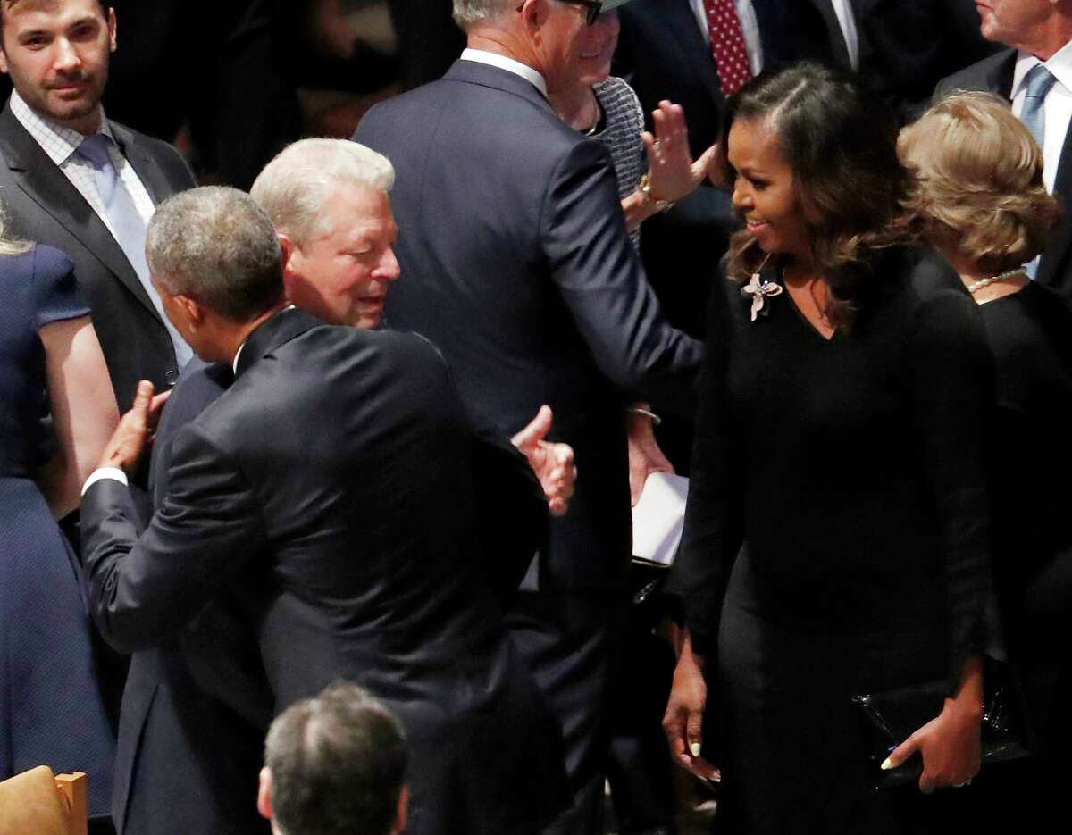 Former President Barack Obama hugs former vice president Al Gore as former first lady Michelle Obama watches before the memorial services for Sen. John McCain, R-Ariz., at Washington Nationals Cathedral in Washington, Saturday, Sept. 1, 2018. McCain died Aug. 25, from brain cancer at age 81.
