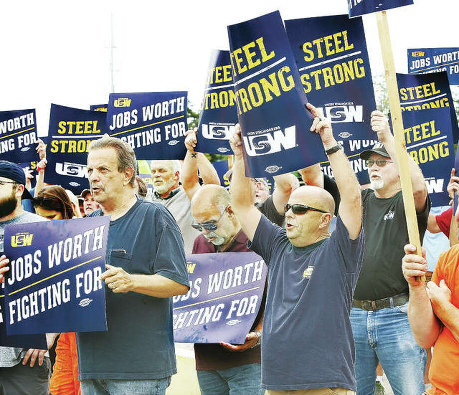 Some of the more than 200 union members who attended a rally Thursday outside the Nash Street gate at Granite City Steel hold signs and repeat chants from union officials. The union is currently negotiating in Pittsburgh, with a contract set to expire on Saturday if no deal is reached. Photo: John Badman | The Telegraph
