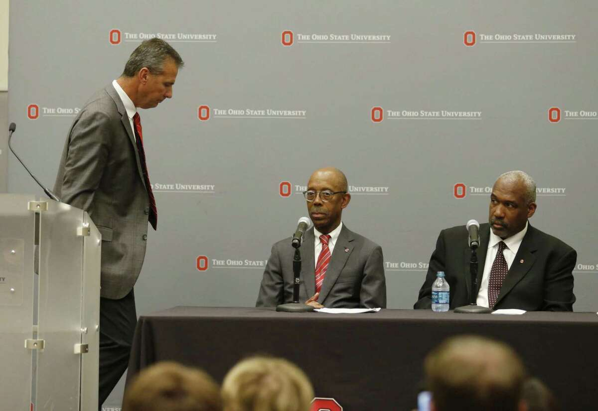 Ohio State University football coach Urban Meyer, leaves the podium after making a statement as university President Michael Drake, center, and athletic director Gene Smith look on during a press conference in Columbus, Ohio, Wednesday, Aug. 22, 2018, to announce the results of an investigation of NCAA college football coach Urban Meyer for the way he handled domestic-abuse allegations against a former assistant.