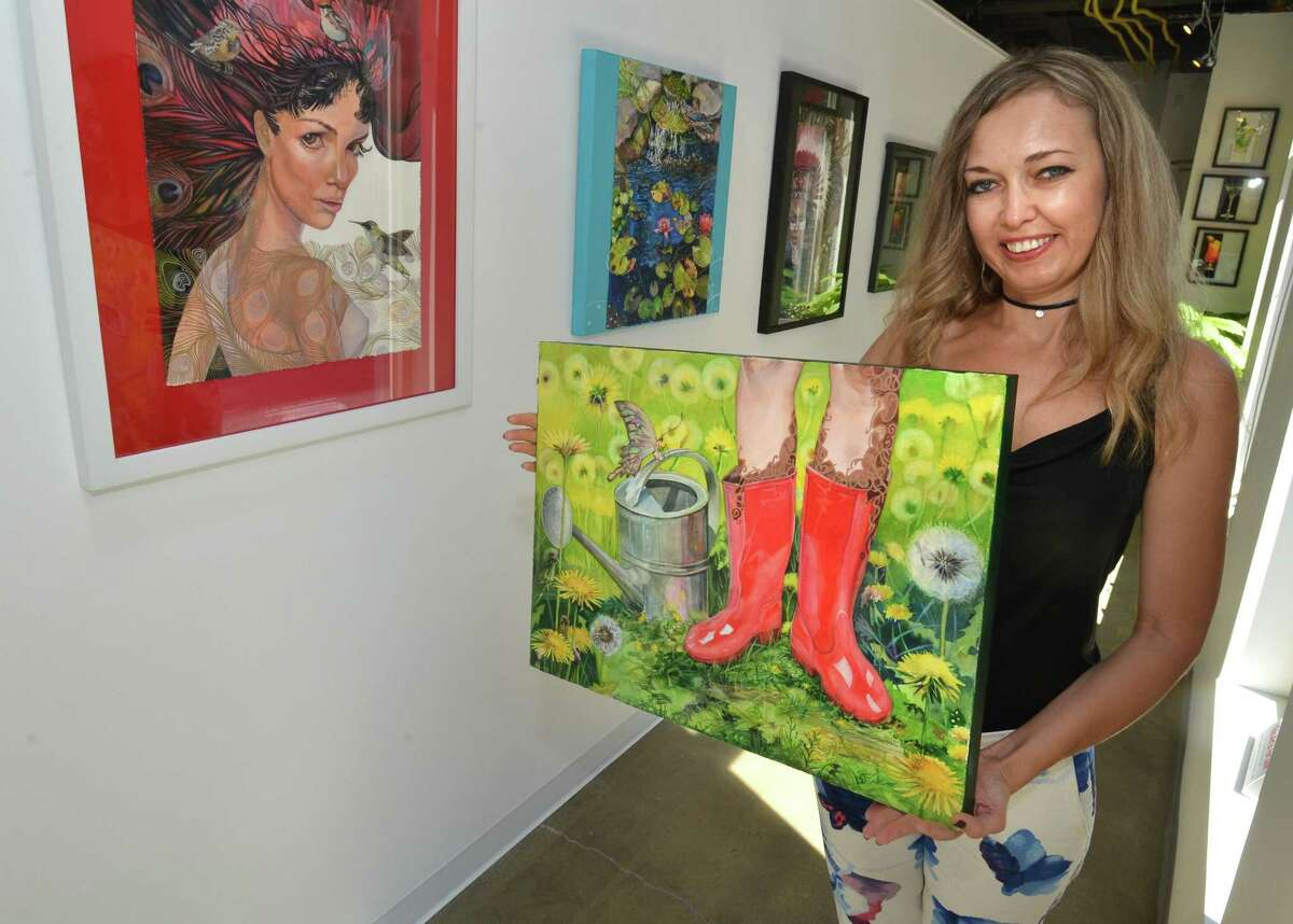 Artist Olga Klymyk stands with one of her watercolors titled Wet Feet just one of 20 included in her exhibit at The Sidewalk Gallery on Thursday August 30 2018. The show is on view until September 30th in Norwalk Conn.