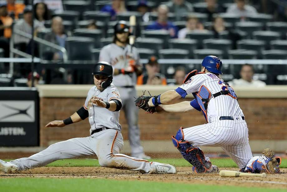 Mets catcher Devin Mesoraco attempts to tag the Giants' Chase d'Arnaud in an Aug. 20 game at New York. Photo: Elsa / Getty Images