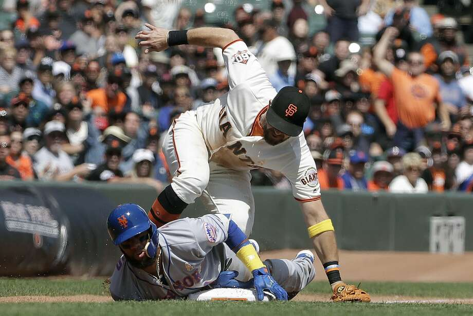 The Mets' Amed Rosario slides safely into third base under the tag of Evan Longoria in the third inning. The Mets tranded Rosario. Photo: Jeff Chiu / Associated Press