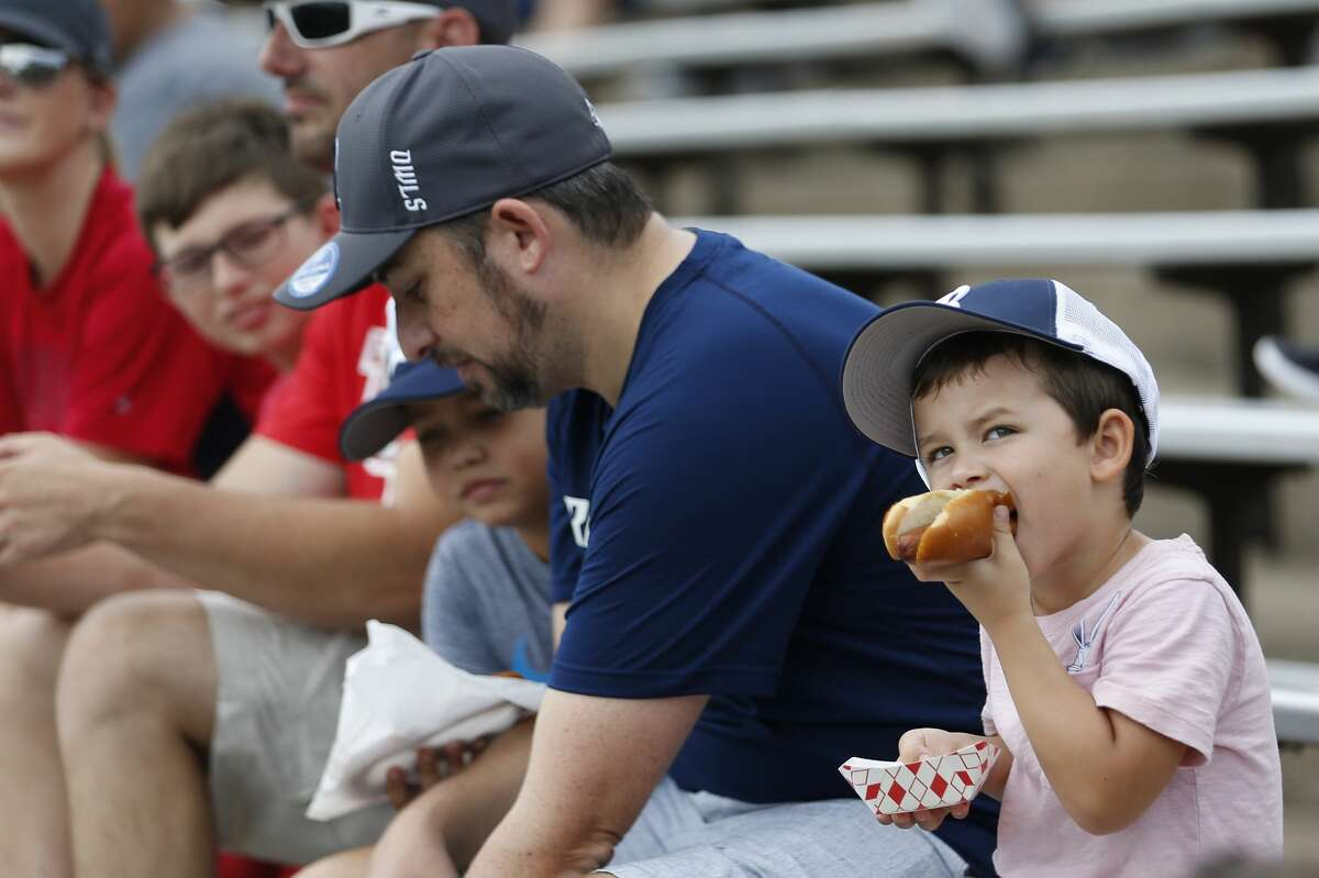 A young Rice fan eats a hot dog during the first quarter of an NCAA football game against Houston at Rice Stadium on Saturday, Sept. 1, 2018, in Houston.