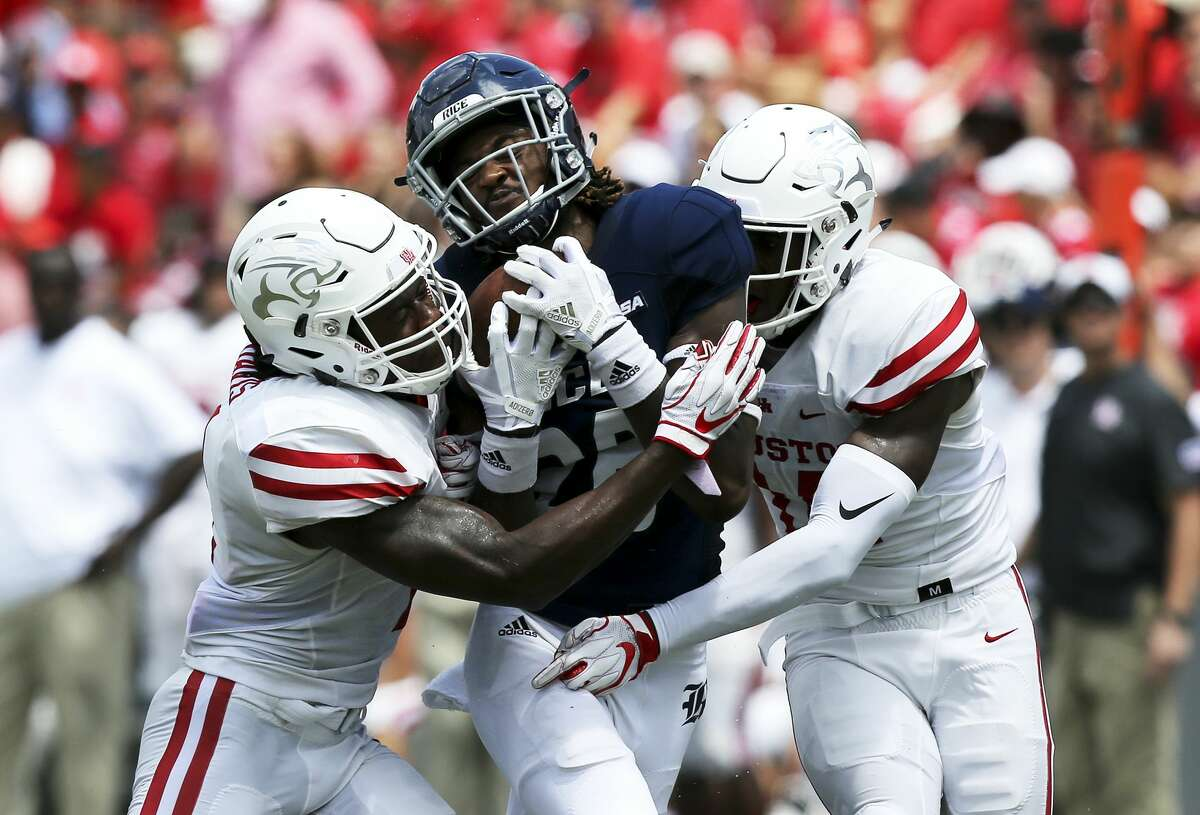 Rice Owls wide receiver Aaron Cephus (28) gets sandwiched between Houston Cougars defensive back Garrett Davis (1), left, and cornerback Isaiah Johnson (14) on Saturday, Sept. 1, 2018 in Houston. Houston Cougars won the game 45-27.