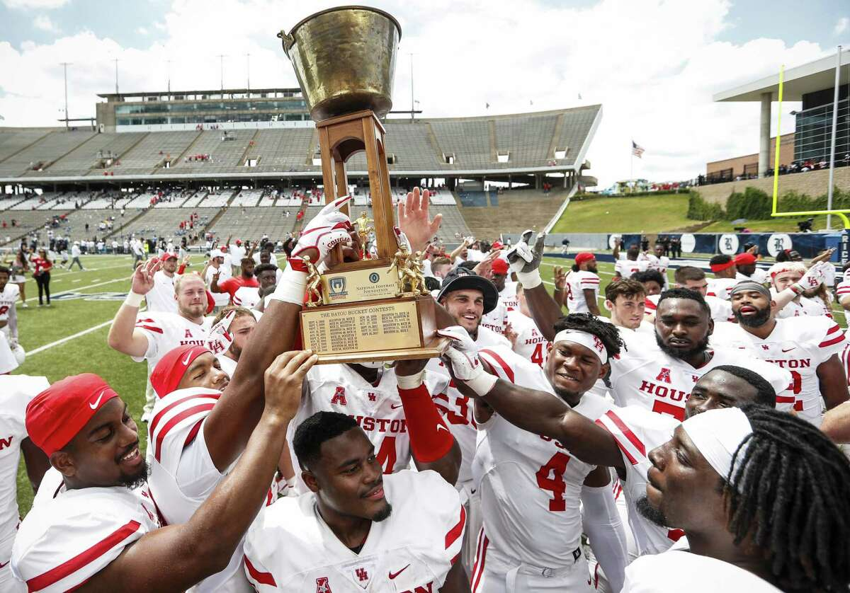 Houston football players hoist the Bayou Bucket after beating crosstown rival Rice 45-27 in an NCAA football game at Rice Stadium on Saturday, Sept. 1, 2018, in Houston.