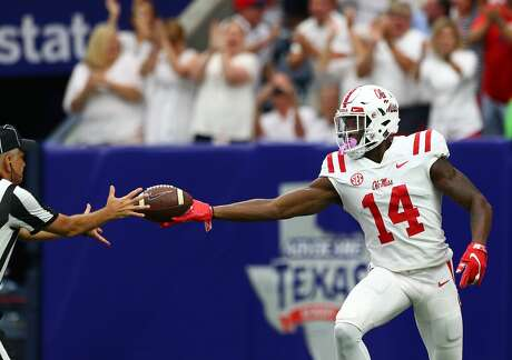 Mississippi Rebels wide receiver D.K. Metcalf (14) hands the ball off to an official after scoring a 58-yard receiving touchdown during the first half of an NCAA game against the Texas Tech Red Raiders at NRG Stadium Saturday, Sept. 1, 2018, in Houston.