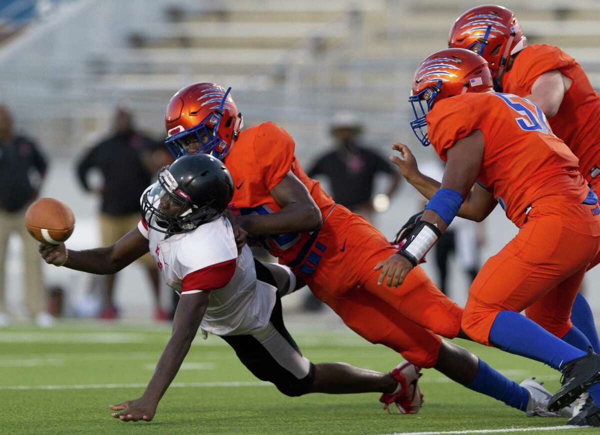 High school football continues to grow in Texas, despite the warnings about safety. Todd Watson, left, competed for KIPP Houston against Grand Oaks in KIPP Houston's first football game Thursday night.