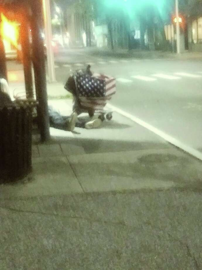 An apparently mentally ill man sleeps on the ground near a bus stop on John Street in downtown Bridgeport. An American flag is draped across his shopping cart. Photo: James Walker / Hearst Connecticut Media /