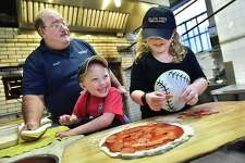 Gary Bimonte, grandson of Frank Pepe, teaches Jack Hanson, 5, and his 8-year-old sister, Eva, how to make a pepperoni pizza at The Original Frank Pepe Pizzeria Napoletano on Wooster Street in New Haven.