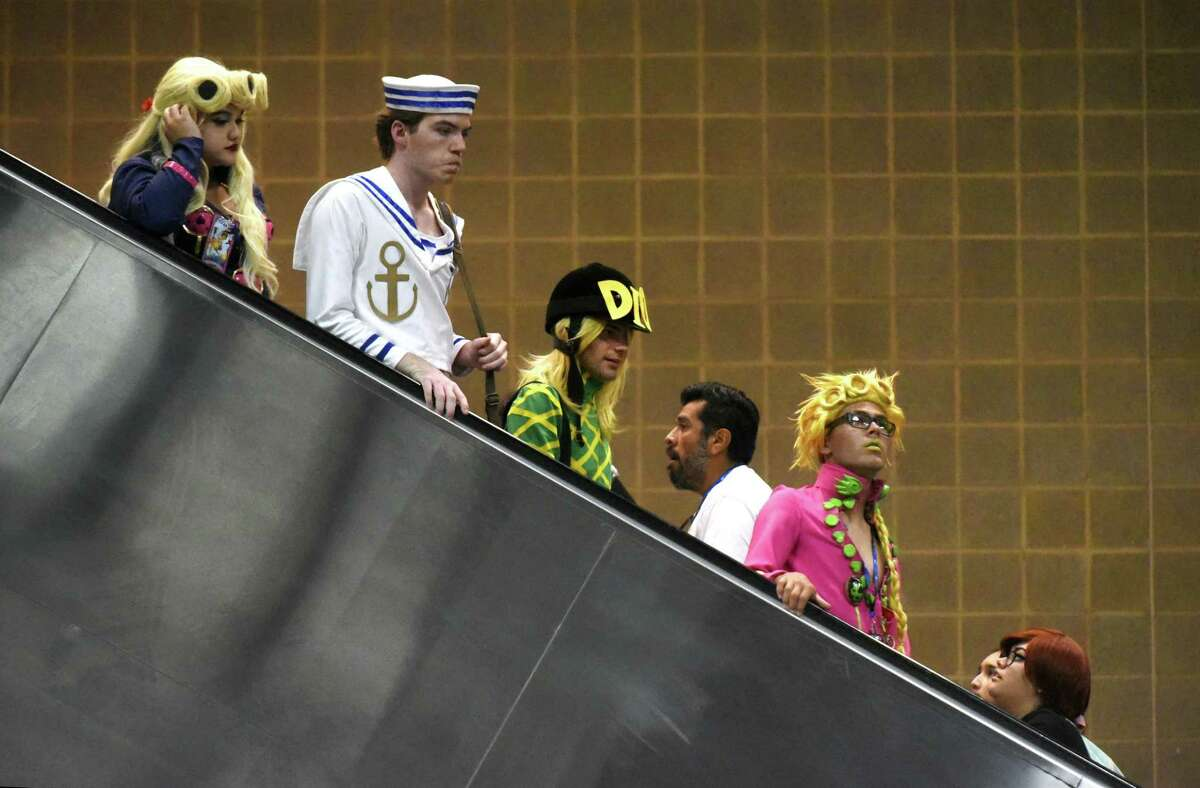 Costumed attendees descend on an escalator Saturday during the San Japan XI: Magical Universe at the Convention Center.