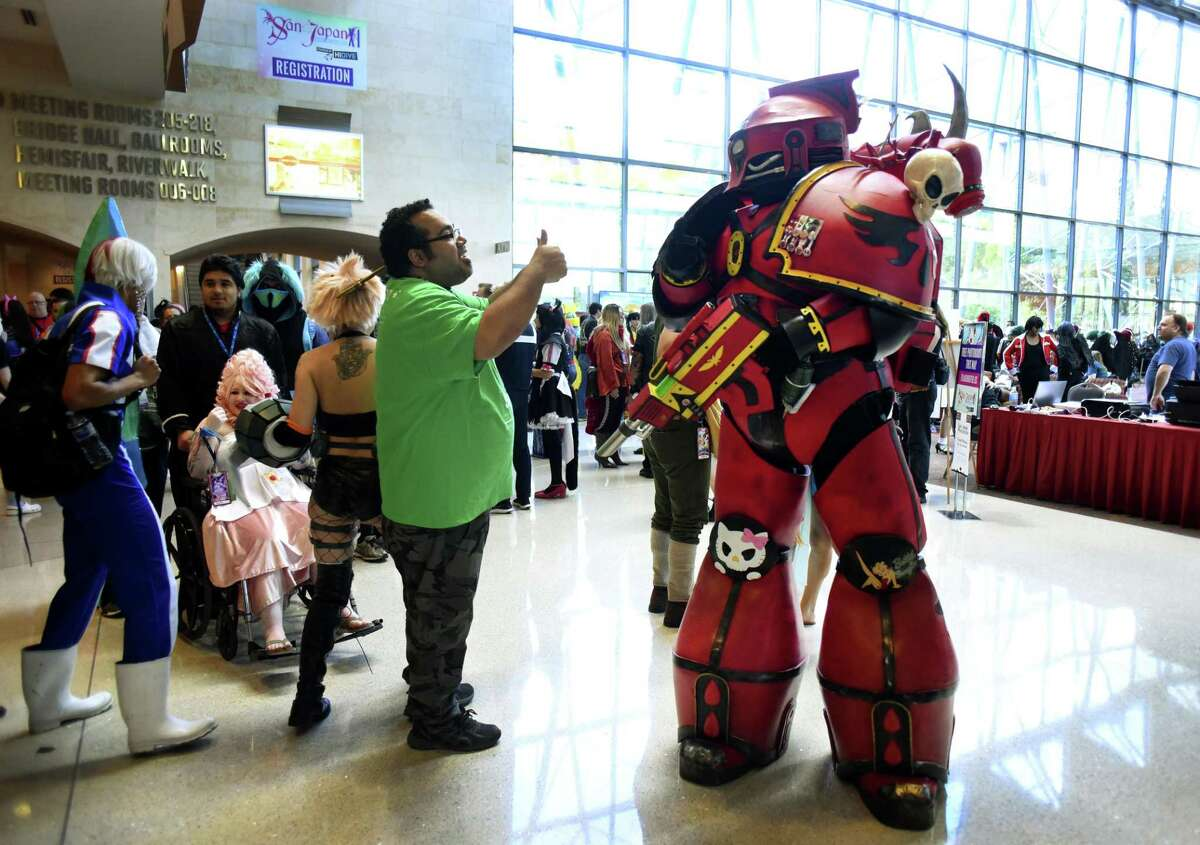 Brian Briggs (right) wears Deadpool armor Saturday during the San Japan anime convention at theConvention Center.